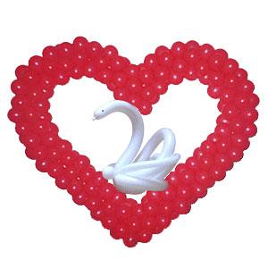 Красное сердце с белым лебедем из воздушных шаров