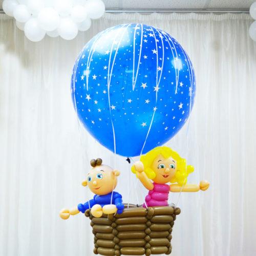 Девочка с мальчиком на воздушном шаре Летает